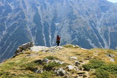 Girl on the top of the Hill. Girl stands on the top of a rocky hill high in the Pirin mountains, Bulgaria Royalty Free Stock Photo