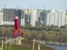Girl from the top looks at the city of Kiev. The girl stands on a hill and admires the city landscape of the city of Kiev. Ukraine Stock Photo
