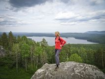 A girl on top of a mountain, in the background of a panorama of mountains and lakes. The girl is happy stock photo