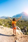 Girl at the top of the mountain. The girl at the top of the mountain raised her hands up. The woman with backpack climbed to the top and enjoyed her success stock image