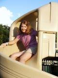 Girl at top of slide. Girl at top of spiral slide royalty free stock image