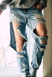 Torn jeans on the girl royalty free stock photography