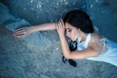 A girl with torn off wings. Fallen Angel. A girl with torn wings, without feelings, lies on the stones, abandoned by God. Artistic Photography Stock Photo