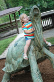 Girl on a Tortoise. A little girl riding a tortise statue Royalty Free Stock Photography
