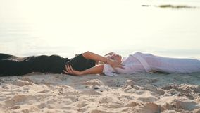 Girl touch each other lying on the sand