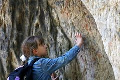 Girl touch a granite rock outdoors Stock Photos