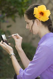 Girl with touch phone. Mobile with yellow hibiscus in hair in the garden stock photography
