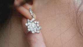 Girl touched the earring with diamond. Hand stock video