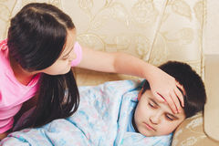 Girl touched his forehead sick brother, checks the temperature. Care in the family Stock Photos