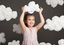 The girl touches the clouds and plays, shot in the studio on a gray background Royalty Free Stock Photography