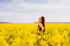 Girl touches her neck on rapeseed meadow Royalty Free Stock Photography