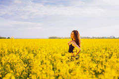 Girl touches her shoulder on rapeseed meadow Royalty Free Stock Images