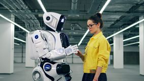 A girl touches white cyborg`s hand, looking at it. stock footage