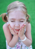 Girl touching her cheeks with hands. Royalty Free Stock Photos