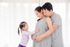 Girl touching her pregnant mother belly and smiles. Little asian girl touching her pregnant mother belly and smiles at home royalty free stock image