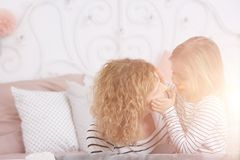 Girl touching mom`s face. Little young girl touching her mom`s face royalty free stock photos