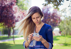 Girl touching phone. Girl in park touching white phone Stock Photography