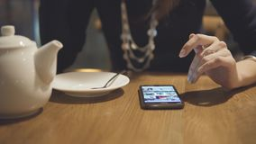 Girl touching the screen with your finger. Woman using her mobile phone in cafe. Girl touching the screen with your finger. Young woman using app on mobile stock footage
