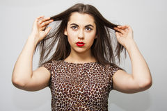 Girl touching tips of  her long hair. Brunette girl looking up and above seroiusly. fashionable makeup with red lips Royalty Free Stock Images