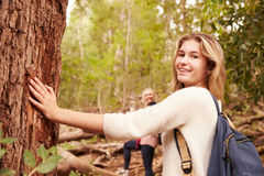 Girl touching a tree in a forest, her mother in the background royalty free stock image