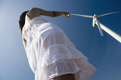 Girl touching the windmill. Crazy perspective of a young woman with white dress trying to touch the blade of a windmill Royalty Free Stock Photos