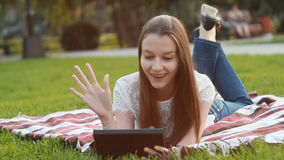 Girl with Touchscreen Tablet Lying on Grass in Sunny Lights stock video footage