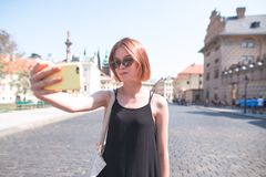 Girl tourist on background takes selfie streets of the old town. Walking along the old city on a sunny summer day royalty free stock photo