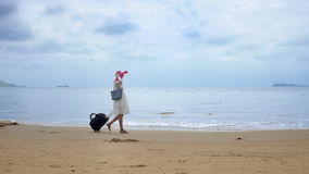 Girl tourist with a bag is walking. Along the beach in Asia stock video footage