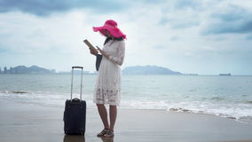 Girl tourist with a big bag is looking in the ipad. Girl tourist with a big bag and in a hat is looking in the ipad for find to hotel stock footage