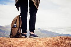 Girl tourist in black sports pants stands on hill. Legs of traveler and backpack with bottle of water close-up royalty free stock images