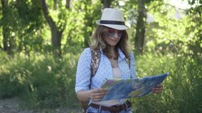 Girl is a tourist chooses a travel destination on the map. a young woman with a backpack walking along the road. Girl traveler wearing sunglasses and a hat stock footage