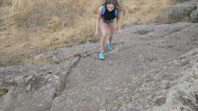 Girl tourist climbs on a rock stock video