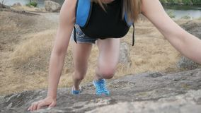 Girl climbs on a rock stock video footage