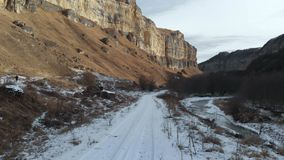 Girl tourist in a down jacket and a cap walks along the path in early winter. Takes a photo on your smartphone epic. Rocks in the gorge. Aerial view stock footage
