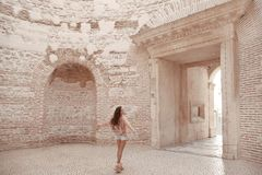 Girl tourist enjoying sightseeing interior door vestibule of the. Girl traveller enjoying sightseeing interior door vestibule of the Diocletian`s palace in old Royalty Free Stock Images