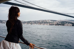 Girl tourist enjoying the view of the city from a boat. Cruise, tour, tourism. Background to the bridge Royalty Free Stock Images