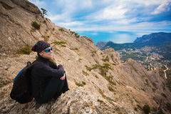 Girl tourist enjoys the view from the mountain top royalty free stock image