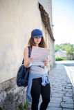 Girl tourist exploring a map near the wall Stock Photo