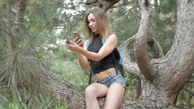 Woman taking selfie. Girl tourist in the forest taking pictures of nature stock video