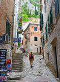 Girl tourist goes on narrow street of Old Town, Kotor, Montenegr Stock Photography