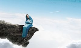 Girl tourist having rest. Mixed media. Young attractive girl in sleeping bag on peak. Mixed media Stock Photos