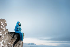 Girl tourist having rest. Mixed media. Young woman in sleeping bag sitting on rock edge. Mixed media Stock Image