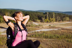 Girl tourist in a hike. Woman tourist in a hike resting in sunlight Stock Photography