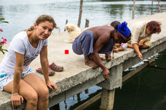 Girl tourist and locals in fisherman's village. Island is on Gulf of Thailand Stock Image