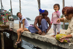 Girl tourist and locals in fisherman's village. Island is on Gulf of Thailand Royalty Free Stock Photos