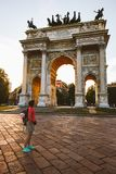 Girl tourist looking atArch of Peace in Sempione Park, Milan, Lombardy, Italy. Arco della Pace aka Porta Sempione in Milan, Italy royalty free stock photo