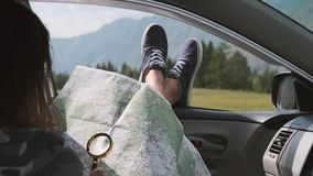 Girl looks at a map using a magnifier while sitting in a car and sticking his legs out the window against the backdrop. Girl tourist looks at a map using a stock footage