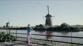 Girl tourist looks at the old windmills in Netherlands stock video footage