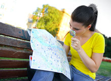 Girl tourist with map on park bench Stock Images