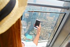 Girl tourist with mobile phone by the window of skyscraper of th. E Burj Khalifa in Dubai, United Arab Emirates, UAE. Close up stock photo